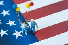 Familia americana feliz miniatura que sostiene los globos que se colocan encendido Uni Fotografía de archivo