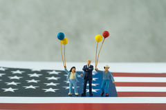 Familia americana feliz miniatura que sostiene los globos que se colocan encendido Uni Imagen de archivo