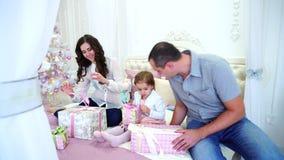 Familia amistosa en el humor festivo para intercambiar los regalos que se sientan en cama en sitio brillante en fondo del árbol d almacen de video