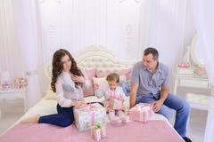 Familia amistosa en el humor festivo para intercambiar los regalos que se sientan en cama Fotos de archivo