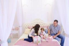 Familia amistosa en el humor festivo para intercambiar los regalos que se sientan en cama Fotos de archivo libres de regalías