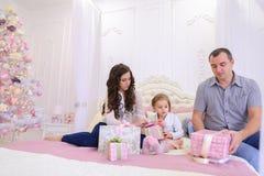 Familia amistosa en el humor festivo para intercambiar los regalos que se sientan en cama Fotografía de archivo