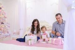Familia amistosa en el humor festivo para intercambiar los regalos que se sientan en cama Imágenes de archivo libres de regalías