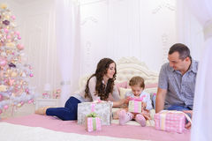 Familia amistosa en el humor festivo para intercambiar los regalos que se sientan en cama Imagenes de archivo
