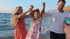 Familia amistosa que camina a lo largo de la costa en lento almacen de metraje de vídeo