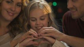 Familia amistosa que hace el corazón con las manos, el amor y el cuidado, celebración de la Navidad almacen de video