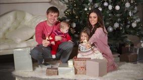 Familia amistosa que se sienta cerca del árbol de navidad y que lleva a cabo las luces de Bengala en su mano almacen de video
