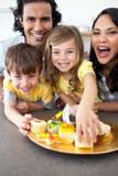 Familia animada que come las galletas Imagenes de archivo