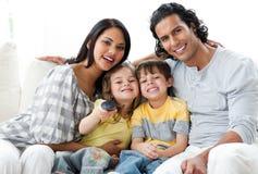 Familia animada que ve la TV junto Imagen de archivo