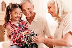 Familia armoniosa que emite mientras que mira en el juguete del robot junto imágenes de archivo libres de regalías