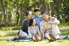 Familia asiática con dos niños que charlan el parque fotos de archivo libres de regalías