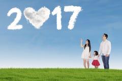 Familia asiática con el número 2017 en prado Foto de archivo