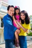 Familia asiática con el niño que se coloca delante de hogar imagen de archivo libre de regalías