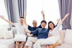 Familia asiática con los niños adultos y los padres mayores que aumentan las manos para arriba y que se sientan en un sofá en cas Imagenes de archivo