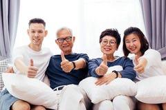 Familia asiática con los niños adultos y los padres mayores que dan los pulgares para arriba y que se relajan en un sofá en casa  Imagen de archivo libre de regalías