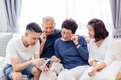 Familia asiática con los niños adultos y los padres mayores que usan un teléfono móvil y relajándose en un sofá en casa junto Imagenes de archivo