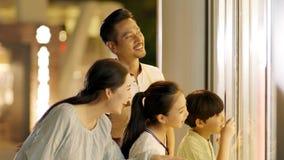 Familia asiática de 4 que se colocan y que miran en ventana de la tienda en la cámara lenta metrajes