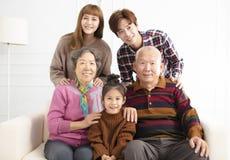 Familia asiática feliz en el sofá foto de archivo libre de regalías