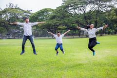 familia asiática feliz, padres y sus niños saltando junto en parque madre e hijo del padre que se divierten y que r?en al aire li fotografía de archivo