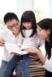 Familia asiática feliz que estudia junto Imágenes de archivo libres de regalías