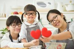 Familia asiática feliz que lleva a cabo corazones rojos mientras que cuece las galletas y c Fotografía de archivo