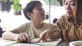 Familia asiática feliz que mira el menú en restaurante, cámara lenta 4k metrajes