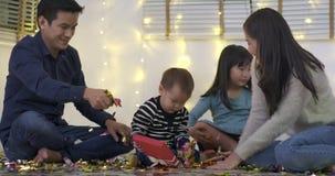 Familia asiática feliz que se sienta en piso en sala de estar y que juega con confeti almacen de metraje de vídeo