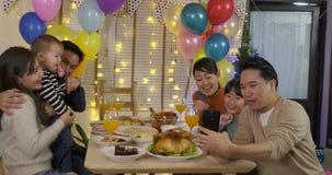 Familia asiática feliz que toma la foto del selfie en una fiesta de Navidad metrajes