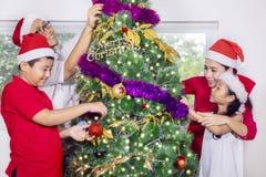 Familia asiática que adorna un árbol de navidad en casa Fotografía de archivo libre de regalías