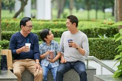 Familia asiática que bebe en parque foto de archivo libre de regalías