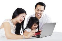 Familia asiática que compra en línea Fotos de archivo libres de regalías