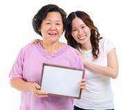 Familia asiática que lleva a cabo a una tarjeta en blanco Foto de archivo
