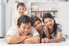 Familia asiática que presenta en el suelo Imágenes de archivo libres de regalías