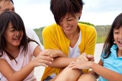 Familia asiática que ríe y que juega en la playa Imagen de archivo