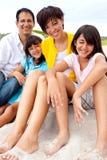 Familia asiática que ríe y que juega en la playa Imagen de archivo libre de regalías