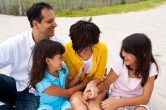 Familia asiática que ríe y que juega en la playa Imágenes de archivo libres de regalías