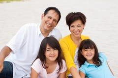 Familia asiática que ríe y que juega en la playa Imagenes de archivo