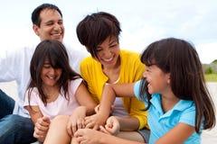 Familia asiática que ríe y que juega en la playa Foto de archivo libre de regalías