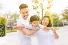 Familia asiática que se divierte y que lleva a un niño en parque público imagenes de archivo