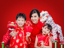 Familia asiática que sostiene el dinero rojo del paquete fotografía de archivo libre de regalías