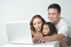 Familia asiática usando la computadora portátil Foto de archivo libre de regalías