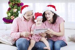 Familia asiática usando una tableta en el tiempo de la Navidad Foto de archivo libre de regalías