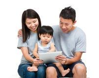 Familia asiática con el hijo de la madre, del padre y del bebé que usa el toget de la tableta Foto de archivo libre de regalías