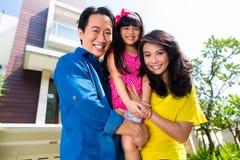 Familia asiática con el niño que se coloca delante de hogar Imágenes de archivo libres de regalías