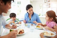 Familia asiática que se sienta en la tabla que come la comida junto Foto de archivo libre de regalías