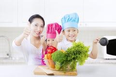 Familia atractiva con las verduras y el pulgar para arriba Foto de archivo
