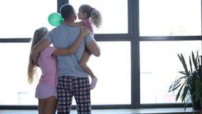 Familia atractiva en abrazo del amor por la ventana almacen de metraje de vídeo