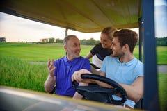 Familia atractiva en su carro de golf Imagenes de archivo