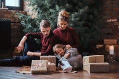Familia atractiva que se sienta junto en un piso rodeado por los regalos al lado del árbol de navidad imágenes de archivo libres de regalías