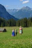 Familia bávara joven en un paisaje hermoso de la montaña Imagen de archivo